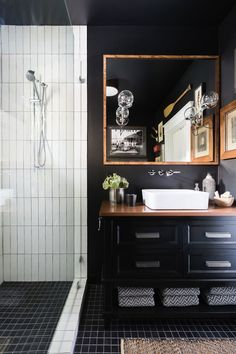 Moody bathroom with black walls, a white shower, a bronze square mirror, and a black vanity with a white modern sink