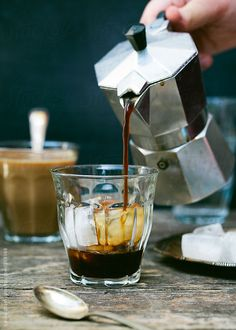 Pouring cold coffee in a glass with ice cubes from mocha pot by Laura Stolfi for Stocksy United
