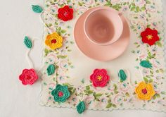 A vibrant garland of crocheted flowers brightens up the breakfast table.