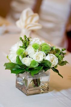 DIY rose centerpiece, you will need a cube vase, short white roses, green carnations and greenery. Lots of other cheap DIY rose centerpieces at http://www.cheap-wedding-solutions.com/diy-wedding-centerpieces-roses.html