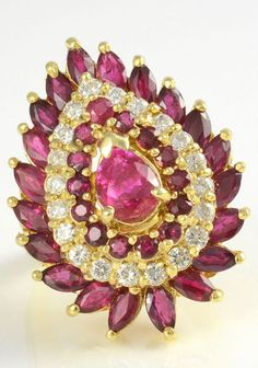 Vintage GIA certified Burmese ruby ring with diamonds, circa 1960. The ring is set in 14 karat yellow gold with a GIA certified 1.10 carat pear shape natural Burmese ruby with round and marquise accent rubies at 3.42 carat total weight and 20 round brilliant diamonds at 0.62 carat total weight SI2 clarity G color.