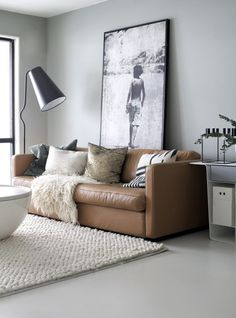 Tan leather sofa with oversized photograph and white rug