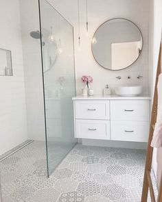 Contemporary shower drain. Simple shower glass. Round mirror. Cool pendant lighting.