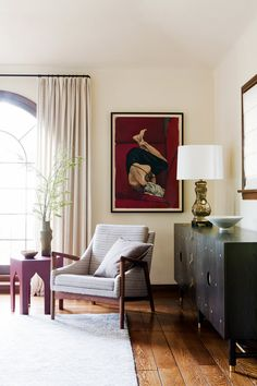 Reading corner in living room with neutral armchair, red antique art, and branch in vase