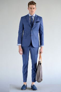 WHAT IS OUR WORLD COMING TO? that's not even a man bag. that's a straight up purse. and his suit looks like he is trying to fit into the one he got when he turned 14.