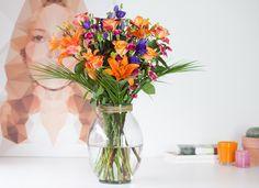 Boeket Zonneschijn <3 Bezorg de zon op tafel met dit feestelijke boeket Zonneschijn! Maak iemand erg blij en vrolijk met een waaier kleurige bloemen. Hoe ziet zonneschijn op de vaas er uit? Oranje rozen en lelies, blauwe en rosita lisianthus met roze trosanjers tussen groen Roebelenii-blad.