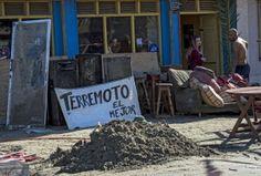 """Residentes mueven sus muebles hacia un anuncio de una bebida local, """"Terremoto"""", en Tongoy, un balneario a 400 km al norte de Santiago"""