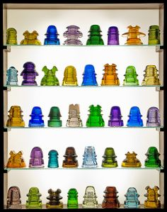 Glass insulators were first produced in the 1850's for use with telegraph lines. As technology developed insulators were needed for telephone lines, electric power lines, and other applications. Today they're collectibles appreciated for their unusual shapes and brightly colored glass.