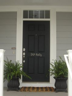 front door decor.  I really want a black front door.  The ferns are great.  And how cute to stencil the number right on the door!  (not like the # is going to change)