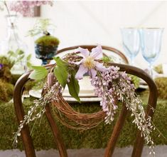 """Soft lavender colored flowers like clematis and wisteria decorate the backs of old-fashioned chairs. Here you can also see the moss """"carpet"""" effect that's on the table."""