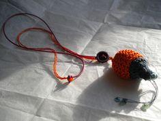Ce sautoir est né d'une promenade sur la plage où je regardais de tout près les boules ovales que forment les algues.  Le tricot permet aussi de sculpter, de retravailler la matière. J'ai joué sur l'association du fil de coton perlé et le fil fin en cuir. L'orangé mêlé à la couleur framboise m'a séduit. Les paillettes bleu lagon, un petit brin d'océan dans les mains...