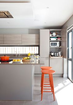 Grey is a fabulous neutral that mixes well with wood and can take a bright accent colour such as this vibrant orange. See more kitchen inspiration at kitchensourcebook.co.uk.
