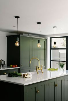 This Shaker kitchen t has been painted in a bespoke shade, a beautiful dark olive that works so well with the aged brass hardware and tap. The three hanging pendant bulbs are a cool addition and add a modern touch to this space. Dark Green Kitchen, Green Kitchen Cabinets, Gold Kitchen, Kitchen Cabinet Colors, Kitchen Colors, Home Decor Kitchen, Kitchen Furniture, Kitchen Interior, Furniture Stores