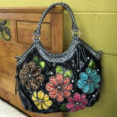 3D Flower Purse Black with gray decorative trim Flowers have a 3 dimensional look adorned with silver grommets Buckles on the sides Zip pocket on the back Inside lining is hot pink and has a zip pocket and three slot pockets for phone etc... Unique in design Matches everything Excellent  condition with the exception of one small mark on the inside lining Boutique Bags Shoulder Bags