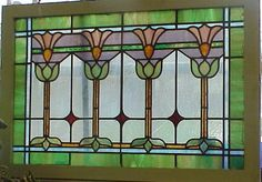 c1910 Arts & Crafts leaded glass window. Fine stained glass workmanship, outer section is slag green with blue and white slag cross sections. The center section is wavy opalescent with 3 ruby red diamonds. The main decoration are 4 stylized arts & crafts flowers. These are green/blue bases, yellow stems and green/wh opalescent to yellow 7 pink petals. The window has been reframed in pine & painted white as original was rotted. The glass leading is tight, there are some cracks to glass but…