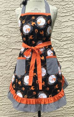 Experience the Nightmare Before Christmas fever in this delightful ruffled apron. A double ruffle in orange and black/white stripe is featured. The neck ties are in black and white striped fabric but the long waist ties (and neckline trim) show a blast of orange. as does the band at
