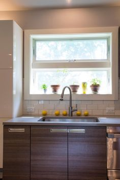A small window casts natural light over this polished kitchen sink area. Woodgrain cabinetry and a neutral countertop surround the stainless steel sink. A line of lemons add natural decoration and color.