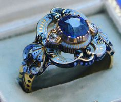 A ring of gold and light blue, black and white enamel, a cushion cut sapphire with on both sides a diamond, in neo-renaissance style, signed C.G. for Carlo Giuliano, London, ca 1890. In original case by Guichard.