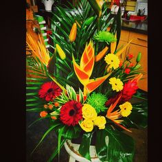 A #lush #tropical #arrangement in nice #warm #tones! Quite #exotic with birds of paradise, gerberas, fuji mums, spray roses, lilies and greens!