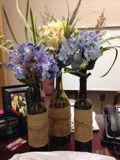 Recycled wine glasses with burlap and twine. Filled with a mix of sophisticated,wild flowers. Centerpiece for moms 50th birthday!