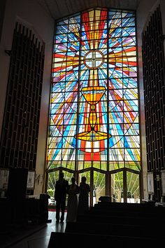 Bride walking down aisle with stained glass