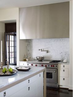 interesting minimalistic camouflage for the vent hood, love the hardware and marble backsplash.