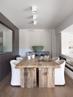 The dining area is a mix of traditional and modern, a great marriage of sleek white dining chairs with the large wooden rustic table. Not to distract from this distinctive piece of furniture, the rest of the decor is kept very simple, with minimalistic lighting and the amount of decorative objects as minimal as possible