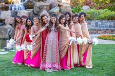 Tanya looked stunning in a traditional Indian dress with vibrant red and gold details. Bridesmaids wore pink-and-gold saris that perfectly complemented her bridal look. #bridesmaids Photography: Yogi Patel - Global Photography. Read More: http://www.insideweddings.com/weddings/indian-wedding-with-vibrant-colors-and-gorgeous-red-roses/639/