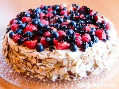 """Her har du en sommerlig festkake! Kaken består av en saftig mandelkake som fylles med deilig vaniljekrem. På toppen dekkes kaken med friske bær, som gjerne kan glaseres med litt solbær- eller ripsgelé for å gi kaken en ekstra delikat """"look""""."""