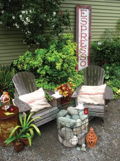 ...weathered chairs w/ pillows, old rusted barrel, rock & glass table. Like the look and feel of this....relax!