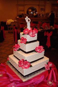 White wedding cake. Buttercream frosting and designs with black ribbon and hot pink roses. www.sugarhillsbakery.com