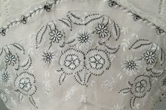 Designer Lucille Date Made 1915 Two piece summer dress of white cotton organdy embroidered in black and white flowers. Accents include skirt is trimmed in lace and shawl collar. Detail
