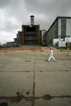 """Chernobyl plant worker Sergei Koshelev crosses the high-radiation zone beside Chernobyl's ground zero. The concrete and lead Sarcophagus encloses the ruins of the reactor hall where the meltdown occurred. The Sarcophagus leaks and is structurally unstable. Construction workers preparing foundations for a replacement """"New Safe Confinement"""" can hit their maximum daily dose in two to three hours. Photo: Michael Forster Rothbart"""