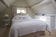 Vaulted bedroom with wooden beams, kingsize bed and crisp white cotton sheets.