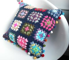 Crochet cushion with multi-coloured pompoms