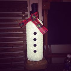 """Snowman wine bottle:) pretty simple I took an empty wine bottle sprayed it with a matte white paint then sprayed it with a """"flurry"""" white spray from michaels then sprayed again with the matte to seal it in...black buttons a piece of fabric and topped it off with black twine on the top:)"""