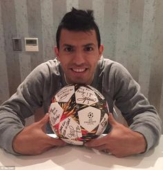 Sergio Aguero smiles for the camera as he poses with the match ball after his Manchester C...