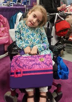 A young girl shows off the Princess Damask wheelchair bag at the NY/NJ Abilities Expo. (2015 NY/NJ Abilities Expo)