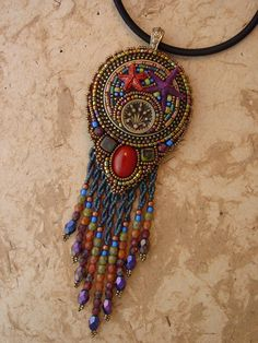 This wonderful necklace with some awesome twisted fringe. The center is a mosaic setting using epoxy clay to set a vintage button, beads and some starfish. The pendant measures 5  long x 1 3/4 wide and hangs from a 16 beaded chain.