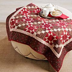 Alternate Sawtooth Star and Double Four-Patch blocks in rich reds and browns for a cozy throw.