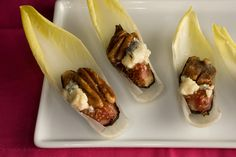 Endive with Figs, Blue Cheese, and Pecans: •1 tablespoon unsalted butter •24 pecan halves •1 tablespoon granulated sugar •1 tablespoon packed light brown sugar •1 tablespoon maple syrup •6 fresh figs •2 tablespoons extra-virgin olive oil •Salt •Freshly ground black pepper •3 heads Belgian endive •1/2 cup crumbled blue cheese
