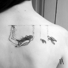 A small sexy tattoo in the upper part of the back in which a girl dives with turtles looks very seductive.