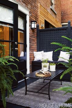 Homeowners Priscilla and René Wikkerink built their fence with sections of lattice — all stained a dramatic opaque black — boxed in with frames and posts. | Design: Terry Ryan Photographer: Angus Fergusson