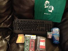 Woot Dec 2016 BOC: green bag, gaming keyboard, BOC sticker, 2 bungie cords, drill bits, hallogen light bulb, and cereal on the go container.