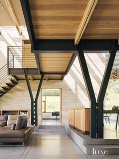 Because there is a change of grade from one side of the house to the other, the architect elevated the dining area two steps above the living room. A black-acacia buffet built by woodworker Ben Loeser provides a sense of separation between the two spaces.