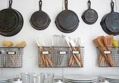 Wall mounted wire baskets for organizing kitchen utensils w/out consuming precious counter space.