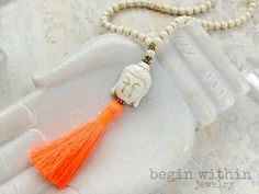 Tap into inner peace with this calming white buddha tassel necklace made from 108 white magnesite beads, a white magnesite buddha and a bright neon coral tassel. This mala measures approx 30 around and can be customized with either silver or gold plated accents. Magnesite is