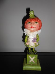 "KELLY WITH A KISS, 9"" tall, 2013 original Debra Schoch St. Patrick's Day girl.  A freckled face ,green eyed ginger girl in her best dress and apron and hat. A bunch of violets and a kiss ..she has a wee bit o' sparkle glitter and a ruffled crepe paper collar...Mounted on a wood block and base. Antiqued and signed . Paper Clay Material."