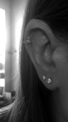 Double lobe piercing with cute hummingbird earring in the cartilage piercing.