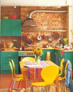 Sea-green cupboard contrast with rich reds and sunny yellows.   Bare brick walls are the starting point for this kitchen, inspiring the bric...